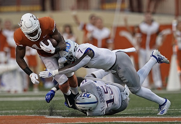Texas's Brennan Eagles (13) is tackled by Kansas's Kyron Johnson (15) and Davon Ferguson (7) during the first half of an NCAA college football game in Austin, Texas, Saturday, Oct. 19, 2019. (AP Photo/Chuck Burton)