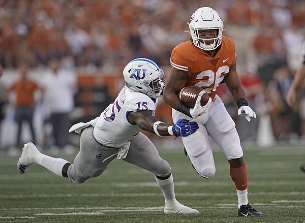 Texas's Keaontay Ingram (26) runs through a tackle of Kansas's Kyron Johnson (15) during the first half of an NCAA college football game in Austin, Texas, Saturday, Oct. 19, 2019. (AP Photo/Chuck Burton)