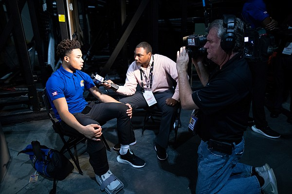 Kansas point guard Devon Dotson sits for an interview during Big 12 Media Day on Wednesday, Oct. 23, 2019 at Sprint Center in Kansas City. Dotson is wearing a boot on his right foot after sustaining an injury during practice on Tuesday.