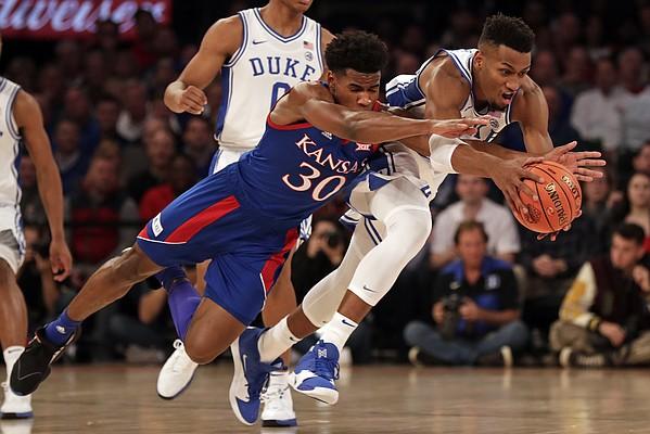 Kansas guard Ochai Agbaji (30) and Duke forward Javin DeLaurier reach for the ball during the first half of an NCAA college basketball game Tuesday, Nov. 5, 2019, in New York. (AP Photo/Adam Hunger)