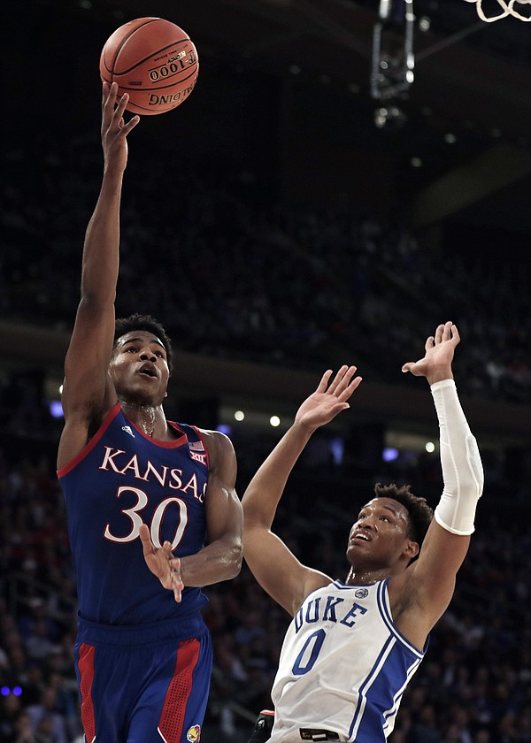 Kansas guard Ochai Agbaji (30) drives to the basket past Duke forward Wendell Moore Jr. (0) during the first half of an NCAA college basketball game Tuesday, Nov. 5, 2019, in New York. (AP Photo/Adam Hunger)