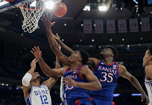 Duke forward Javin DeLaurier (12) vies for a rebound with Kansas forward David McCormack and center Udoka Azubuike (35) during the first half of an NCAA college basketball game Tuesday, Nov. 5, 2019, in New York. (AP Photo/Adam Hunger)