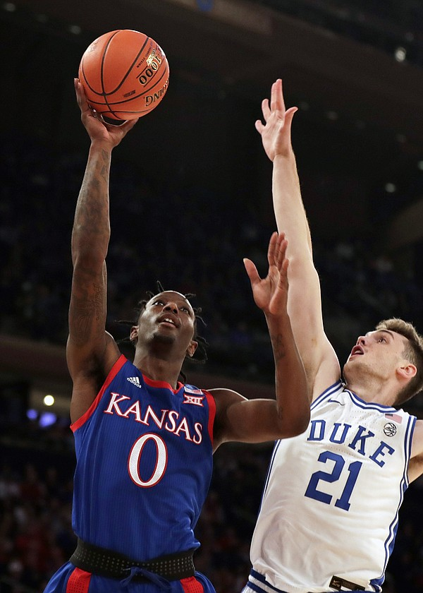 Kansas guard Marcus Garrett (0) drives to the basket past Duke forward Matthew Hurt (21) during the first half of an NCAA college basketball game Tuesday, Nov. 5, 2019, in New York. (AP Photo/Adam Hunger)