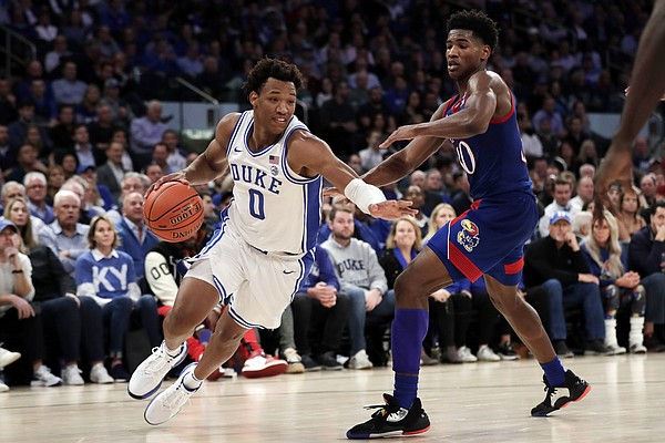 Duke forward Wendell Moore Jr. (0) drives to the basket past Kansas guard Ochai Agbaji during the second half of an NCAA college basketball game Tuesday, Nov. 5, 2019, in New York. (AP Photo/Adam Hunger)