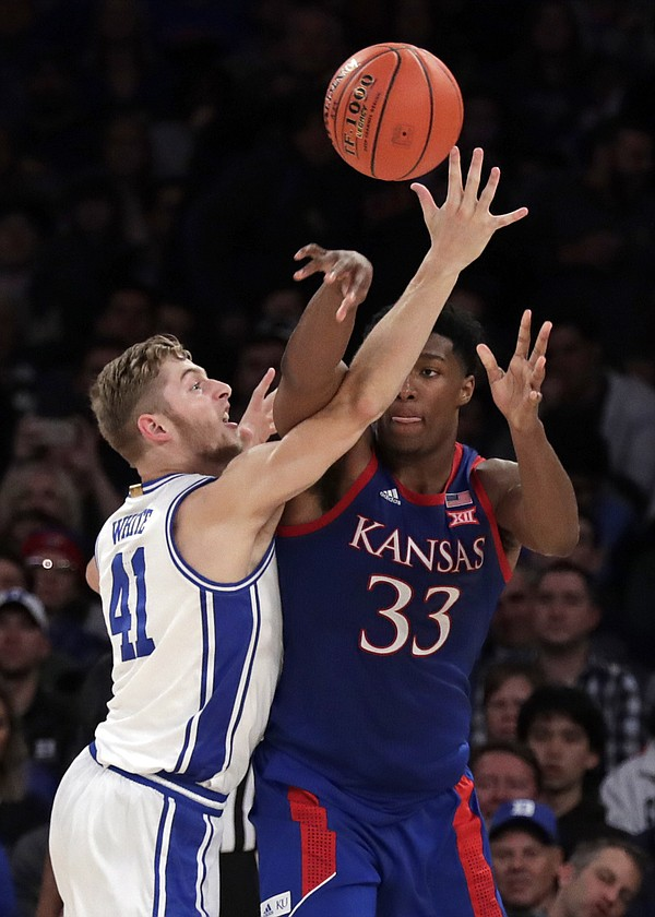 Kansas forward David McCormack (33) passes the ball past Duke forward Jack White (41) during the second half of an NCAA college basketball game Tuesday, Nov. 5, 2019, in New York. (AP Photo/Adam Hunger)