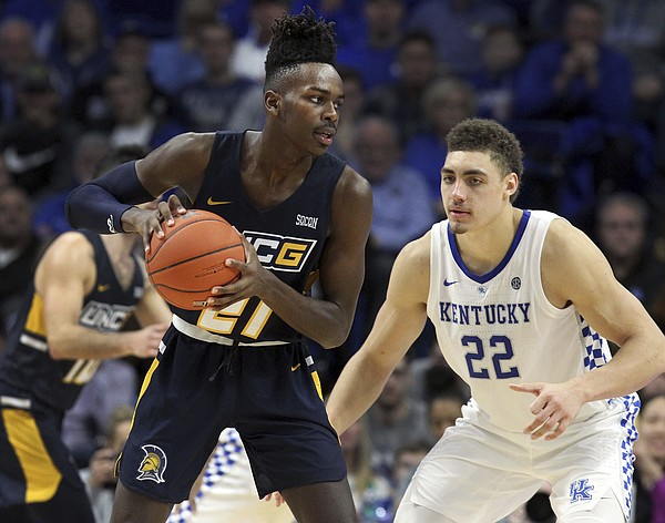 UNC Greensboro's James Dickey, left, looks for an opening on Kentucky's Reid Travis (22) during the second half of an NCAA college basketball game in Lexington, Ky., Saturday, Dec. 1, 2018. Kentucky won 78-61. (AP Photo/James Crisp)