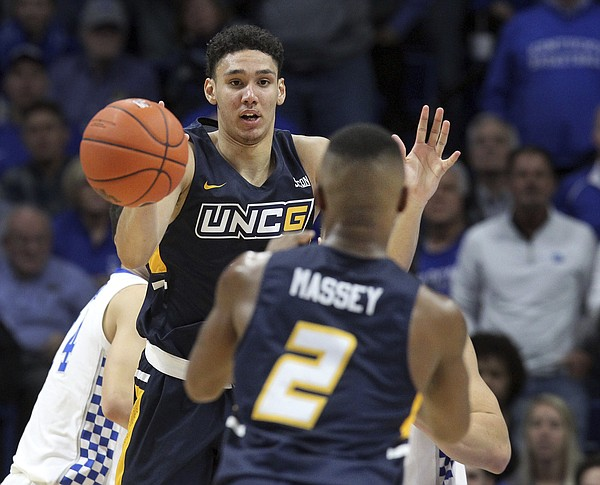 UNC Greensboro's Kyrin Galloway, left, passes to teammate Malik Massey during the second half of an NCAA college basketball game against Kentucky in Lexington, Ky., Saturday, Dec. 1, 2018. Kentucky won 78-61. (AP Photo/James Crisp)