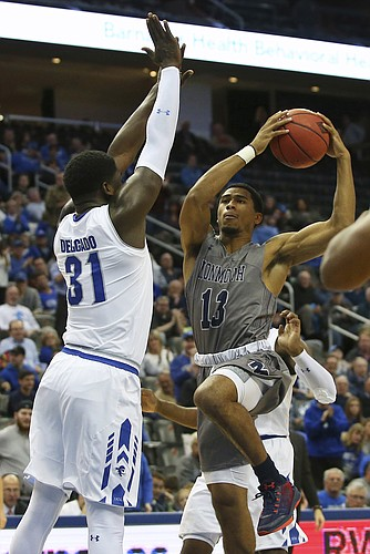 Monmouth's Marcus McClary (13) attempts a shot as Seton Hall's Angel Delgado (31) defends during the first half of an NCAA college basketball game in Newark, N.J., Sunday, Nov. 12, 2017. (AP Photo/Rich Schultz)