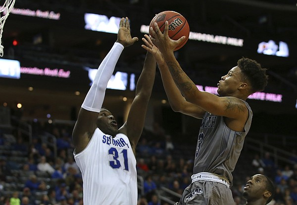 Monmouth's Deion Hammond, right, takes a shot as Seton Hall's Angel Delgado (31) defends during an NCAA college basketball game in Newark, N.J., Sunday, Nov. 12, 2017. Seton Hall defeated Monmouth 75-65. (AP Photo/Rich Schultz)