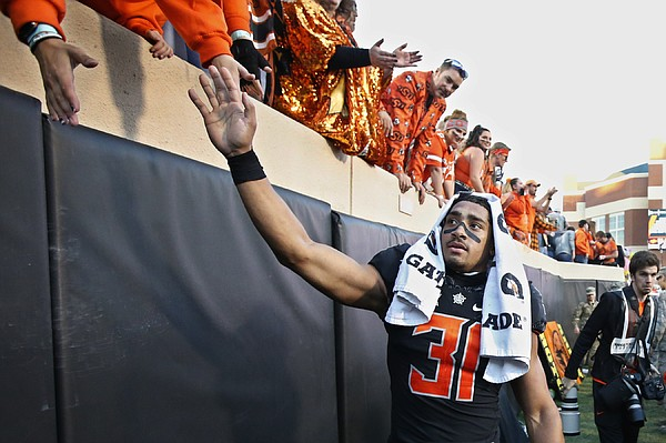 Oklahoma State running back Chuba Hubbard (30) celebrates with fans following an NCAA college football game against TCU in Stillwater, Okla., Saturday, Nov. 2, 2019. Oklahoma State won 34-27. (AP Photo/Sue Ogrocki)