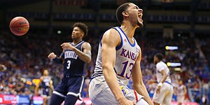 Kansas guard Tristan Enaruna (13) celebrates after a breakaway windmill dunk during the second half against Monmouth on Friday, Nov. 15, 2019 at Allen Fieldhouse.