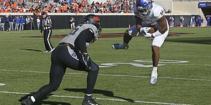 Kansas wide receiver Takulve Williams (16) comes down with a pass reception in front of Oklahoma State linebacker Devin Harper (16) in the second half of an NCAA college football game in Stillwater, Okla., Saturday, Nov. 16, 2019. (AP Photo/Sue Ogrocki)