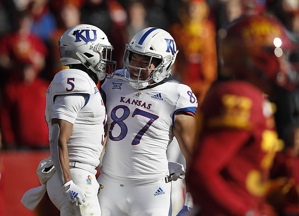 Kansas wide receiver Stephon Robinson, left, celebrates his touchdown with tight end Jack Luavasa, center, during the second half of an NCAA college football game against Iowa State, Saturday, Nov. 23, 2019, in Ames, Iowa. Iowa State won 41-31. (AP Photo/Matthew Putney)