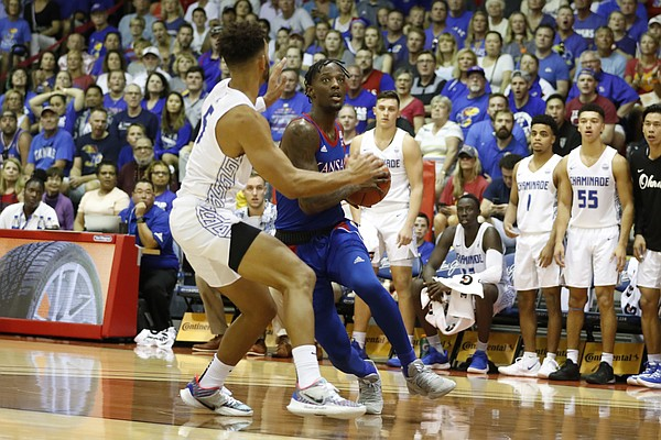 Kansas guard Marcus Garrett (0) tries to get past Chaminade guard Telly Davenport (5) during an NCAA college basketball game Monday, Nov. 25, 2019, in Lahaina, Hawaii. (AP Photo/Marco Garcia)