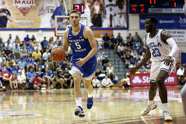 BYU guard Jake Toolson (5) dribbles past UCLA guard Prince Ali (23) during the first half of an NCAA college basketball game, Monday, Nov. 25, 2019, in Lahaina, Hawaii. (AP Photo/Marco Garcia)