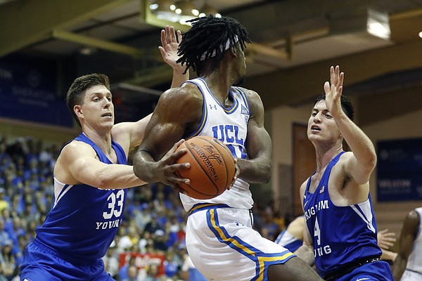 BYU forward Dalton Nixon (33) and guard Alex Barcello (4) defend UCLA forward Jalen Hill (24) during the first half of an NCAA college basketball game, Monday, Nov. 25, 2019, in Lahaina, Hawaii. (AP Photo/Marco Garcia)