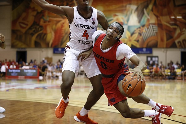 Dayton guard Rodney Chatman (0) falls while being guarded by Virginia Tech guard Nahiem Alleyne (4) during the second half of an NCAA college basketball game Tuesday, Nov. 26, 2019, in Lahaina, Hawaii. (AP Photo/Marco Garcia)