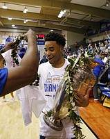 While holding the Maui Invitational trophy, Kansas guard Devon Dotson gets a Hawaiian flower lei Wednesday, Nov. 27, 2019, in Lahaina, Hawaii. Kansas defeated Dayton in 90-84 in overtime in an NCAA college basketball game for the title. (AP Photo/Marco Garcia)
