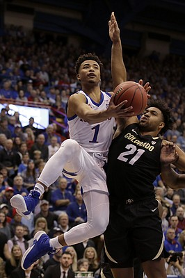 Kansas' Devon Dotson (1) shoots over Colorado's Evan Battey (21) during the first half of an NCAA college basketball game Saturday, Dec. 7, 2019, in Lawrence, Kan. (AP Photo/Charlie Riedel)