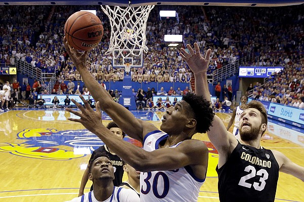 Kansas' Ochai Agbaji (30) gets past Colorado's Lucas Siewert (23) to shoot during the first half of an NCAA college basketball game Saturday, Dec. 7, 2019, in Lawrence, Kan. (AP Photo/Charlie Riedel)