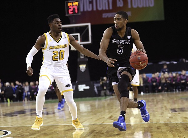 Buffalo's CJ Massinburg, right, drives to the basket against Milwaukee's Darius Roy during the first half of an NCAA college basketball game between the Buffalo Bulls and the Milwaukee Panthers, Friday, Nov. 30, 2018, in Belfast. (AP Photo/Peter Morrison)