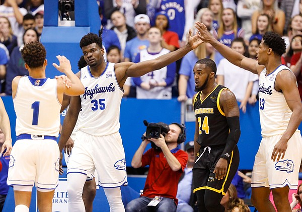 Kansas center Udoka Azubuike (35) slaps hands with Kansas forward David McCormack (33) after Azubuike rejected a shot by Milwaukee guard Josh Thomas (24) during the first half, Tuesday, Dec. 10, 2019 at Allen Fieldhouse.