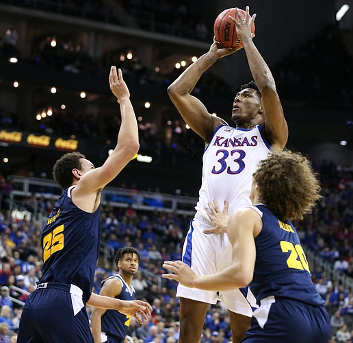 Kansas forward David McCormack (33) pulls up for a shot against UMKC forward Javan White (25) and UMKC forward Josiah Allick (20) during the first half, Saturday, Dec. 14, 2019 at Sprint Center in Kansas City, Mo.