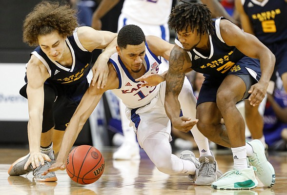 Kansas guard Tristan Enaruna (13) gets on the floor with UMKC forward Josiah Allick (20) and UMKC guard Brandon McKissic (3) for a loose ball during the second half, Saturday, Dec. 14, 2019 at Sprint Center in Kansas City, Mo.