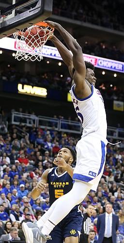 Kansas center Udoka Azubuike (35) extends for a reverse jam as UMKC forward Jordan Giles (5) watches during the second half, Saturday, Dec. 14, 2019 at Sprint Center in Kansas City, Mo.