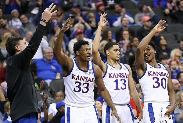 Kansas redshirt Mitch Lightfoot, left, forward David McCormack (33) and guards Tristan Enaruna (13) and Ochai Agbaji (30) celebrate a three from Kansas guard Chris Teahan (12) during the second half, Saturday, Dec. 14, 2019 at Sprint Center in Kansas City, Mo.