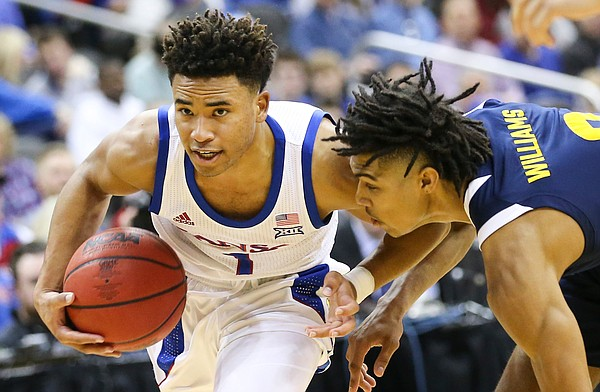 Kansas guard Devon Dotson (1) drives against UMKC guard Zion Williams (0) during the first half, Saturday, Dec. 14, 2019 at Sprint Center in Kansas City, Mo.