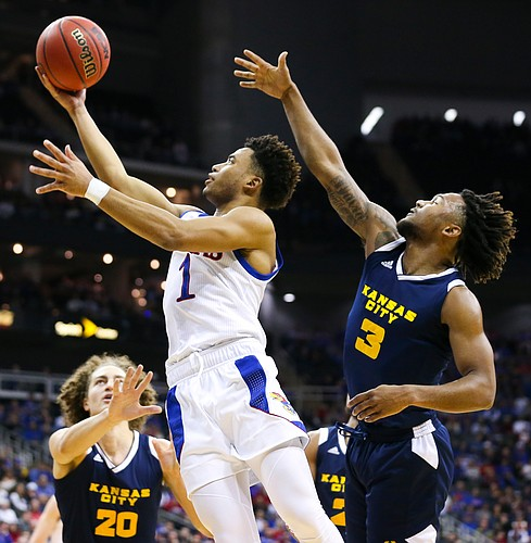 Kansas guard Devon Dotson (1) gets in for a bucket past UMKC guard Brandon McKissic (3) during the first half, Saturday, Dec. 14, 2019 at Sprint Center in Kansas City, Mo. Also pictured is UMKC forward Josiah Allick (20).