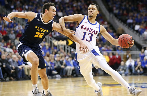 Kansas guard Tristan Enaruna (13) drives against UMKC forward Javan White (25) during the first half, Saturday, Dec. 14, 2019 at Sprint Center in Kansas City, Mo.