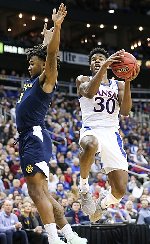 Kansas guard Ochai Agbaji (30) maneuvers around UMKC guard Brandon McKissic (3) for a bucket during the first half, Saturday, Dec. 14, 2019 at Sprint Center in Kansas City, Mo.