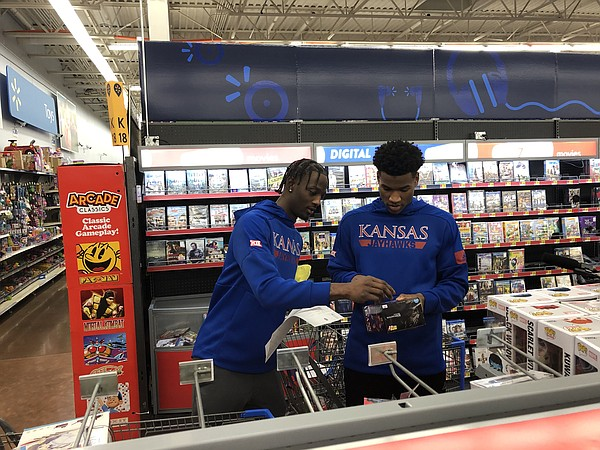 KU guards Marcus Garrett, left, and Ochai Agbaji look over a potential gift during the Jayhawks 23rd annual holiday shopping outing on Tuesday, Dec. 17, 2019 at Walmart in Lawrence.