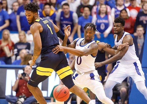 Kansas guard Marcus Garrett (0) knocks the ball loose from West Virginia forward Derek Culver (1) during the second half, Saturday, Jan. 4, 2020 at Allen Fieldhouse.