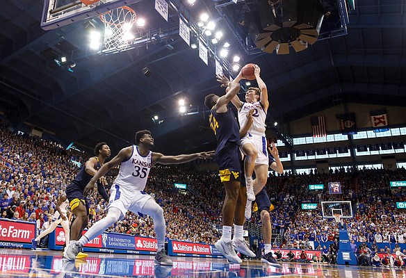 Kansas guard Christian Braun (2) goes hard for a bucket and a foul against West Virginia forward Oscar Tshiebwe (34) during the second half, Saturday, Jan. 4, 2020 at Allen Fieldhouse.