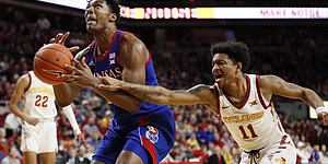 Kansas forward David McCormack drives to the basket ahead of Iowa State guard Prentiss Nixon, right, during the first half of an NCAA college basketball game Wednesday, Jan. 8, 2020, in Ames, Iowa. (AP Photo/Charlie Neibergall)