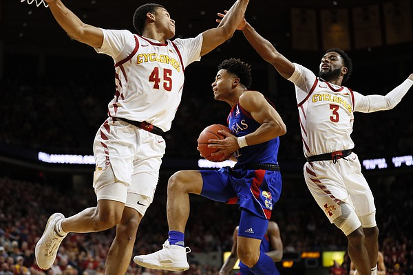 Kansas guard Devon Dotson, center, drives to the basket between Iowa State's Rasir Bolton, left, and Tre Jackson during the first half of an NCAA college basketball game Wednesday, Jan. 8, 2020, in Ames, Iowa. (AP Photo/Charlie Neibergall)