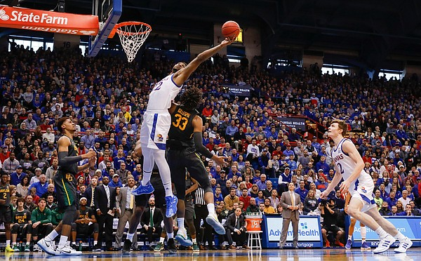 Kansas Jayhawks forward Silvio De Sousa (22) reaches  for a rebound over Baylor Bears forward Freddie Gillespie (33) during the first half on Saturday, Jan. 11, 2020 at Allen Fieldhouse.