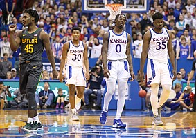 Deflated Kansas players Marcus Garrett (0), Udoka Azubuike (35) and Ochai Agbaji (30) make their way to the bench during a timeout in the second half as Baylor guard Davion Mitchell (45) pumps his fist on Saturday, Jan. 11, 2020 at Allen Fieldhouse.