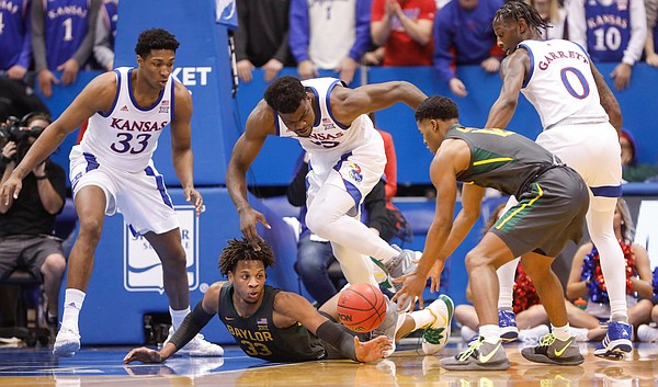Baylor Bears forward Freddie Gillespie (33) flips a loose ball to Baylor Bears guard Jared Butler (12) away from the Kansas defenders during the first half on Saturday, Jan. 11, 2020 at Allen Fieldhouse.