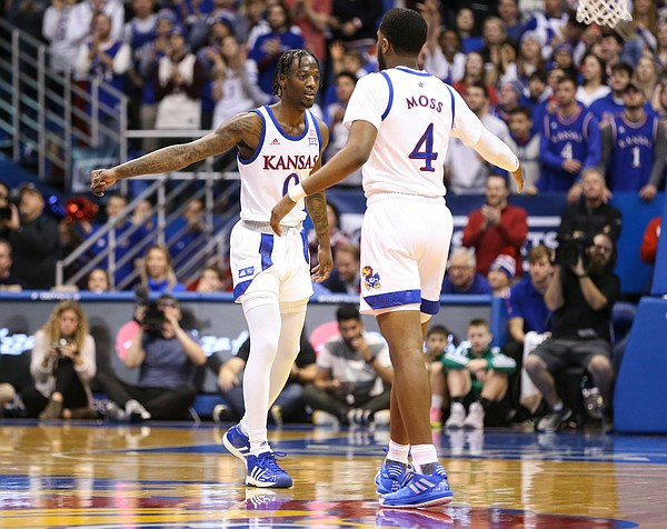 Kansas Jayhawks guard Marcus Garrett (0) and Kansas Jayhawks guard Isaiah Moss (4) slap hands after a three from Moss during the first half on Saturday, Jan. 11, 2020 at Allen Fieldhouse.