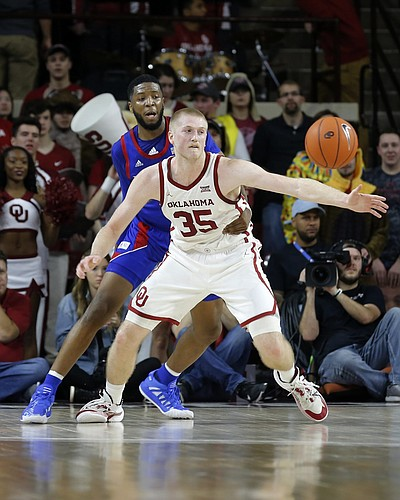 Oklahoma's Brady Manek (35) and Kansas' Isaiah Moss (4) watch the ball during the first half of an NCAA college basketball game in Norman, Okla., Tuesday, Jan. 14, 2020.