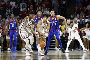 Oklahoma's Jalen Hill (1) and Kristian Doolittle (21) fight for the ball with Kansas' Chris Teahan (12) and David McCormack (33) during the second half of an NCAA college basketball game in Norman, Okla., Tuesday, Jan. 14, 2020. (AP Photo/Garett Fisbeck)