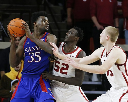 Kansas' Udoka Azubuike (35) is defended by Oklahoma's Kur Kuath (52) and Brady Manek (35) during the second half of an NCAA college basketball game in Norman, Okla., Tuesday, Jan. 14, 2020. (AP Photo/Garett Fisbeck)