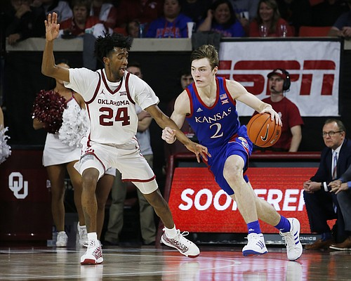 Kansas' Christian Braun (2) is defended by Oklahoma's Jamal Bieniemy (24) during the second half of an NCAA college basketball game in Norman, Okla., Tuesday, Jan. 14, 2020. (AP Photo/Garett Fisbeck)