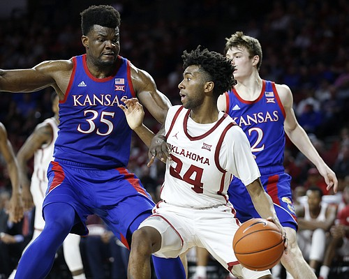 Oklahoma's Jamal Bieniemy (24) is defended by Kansas' Udoka Azubuike (35) and Christian Braun (2) during the second half of an NCAA college basketball game in Norman, Okla., Tuesday, Jan. 14, 2020. (AP Photo/Garett Fisbeck)