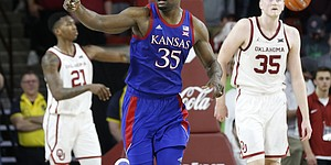 Kansas' Udoka Azubuike (35) gestures near Oklahoma's Brady Manek (35) and Kristian Doolittle (21) during the second half of an NCAA college basketball game in Norman, Okla., Tuesday, Jan. 14, 2020. (AP Photo/Garett Fisbeck)