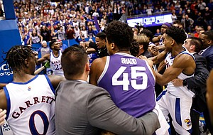 Kansas guard Marcus Garrett (0) and Kansas State forward Nigel Shadd (45) are held back during a brawl following the Jayhawks' win against Kansas State, Tuesday, Jan. 21, 2020 at Allen Fieldhouse.